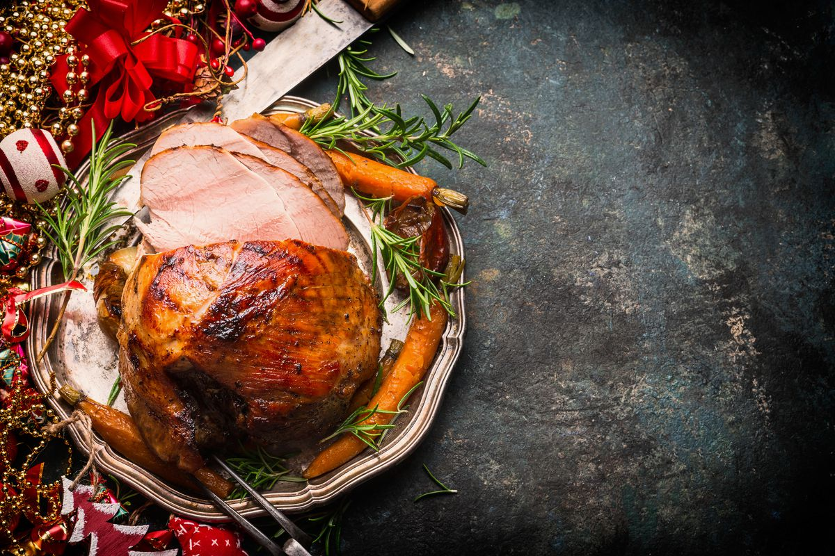 Roast ham decorated with holly and ivy and berries for the holidays