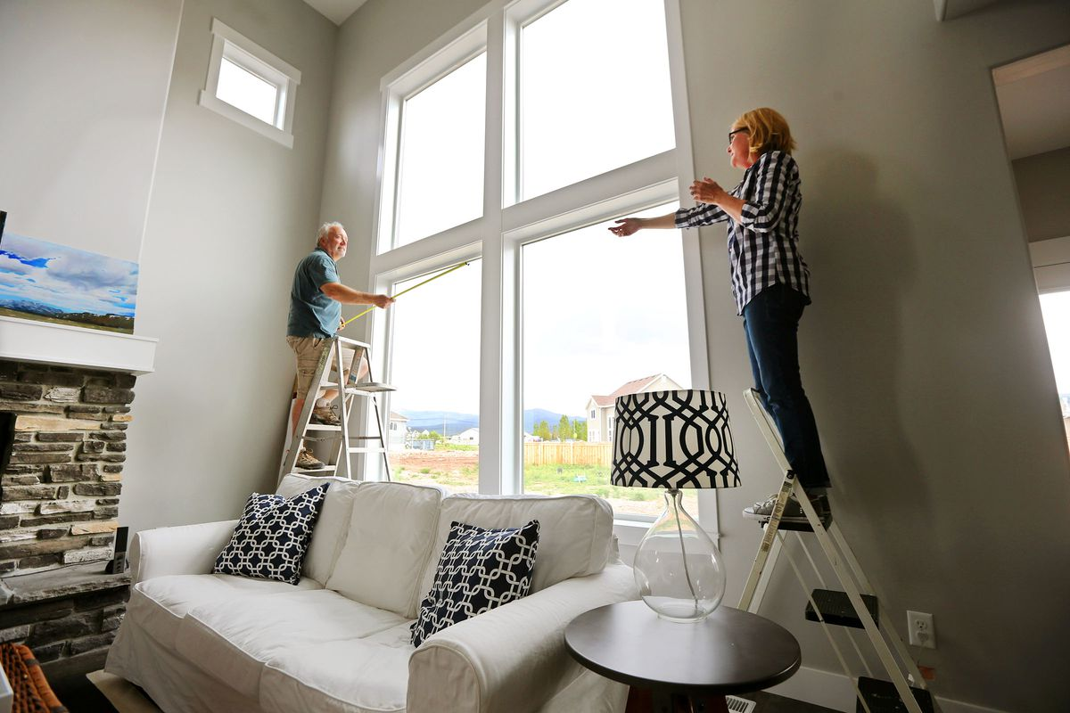Steve and Michelle Allen work to install curtain rods when they first moved in to their Heber City home on May 20, 2015.