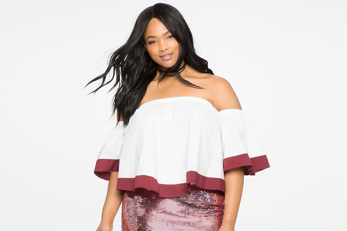 A model in a white and red off the shoulder top and pink skirt