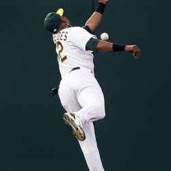 Oakland Athletics center fielder Yoenis Cespedes misses a fly ball hit by the Seattle Mariners' Ichiro Suzuki during the fourth inning of their baseball game in Oakland, Calif., Saturday, April 7, 2012. Suzuki doubled on the play.