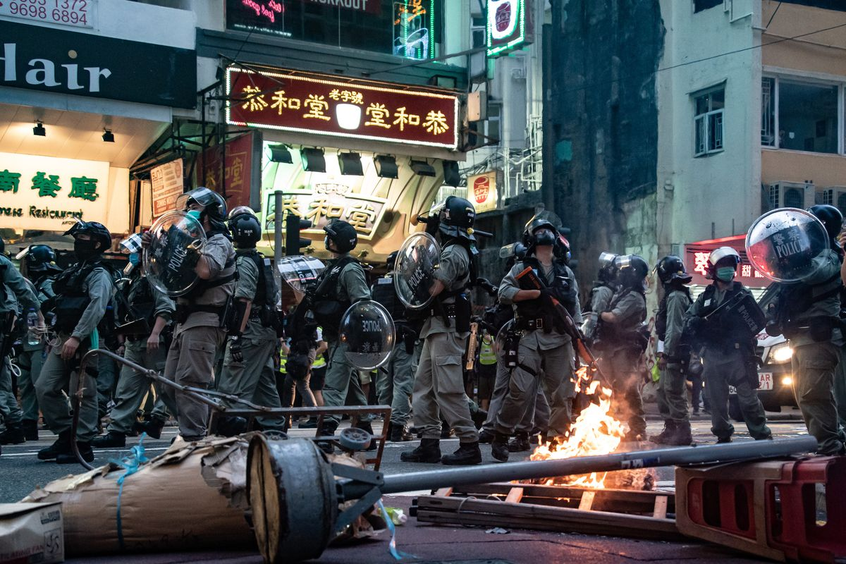 Riot police secure an area in front of a burning roadblock in Hong Kong.