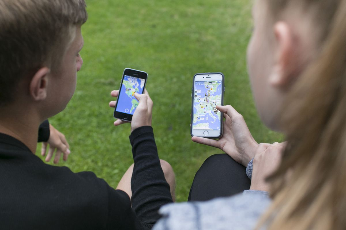 Two people hold smartphones that have maps on their screens.