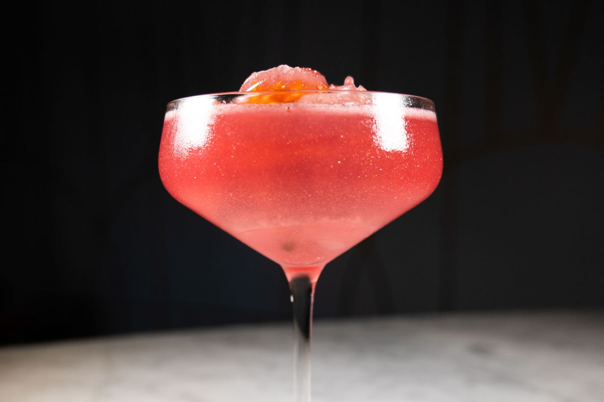 A vivid red cocktail in a coupe set against a black backdrop