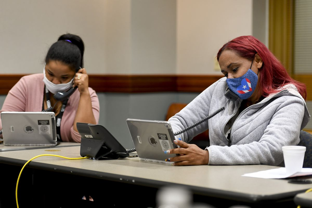 Two women, both in masks, and Arroyo in a pink sweater and Rijos in a grey hoodie, sit in front of iPads while speaking on the phone.