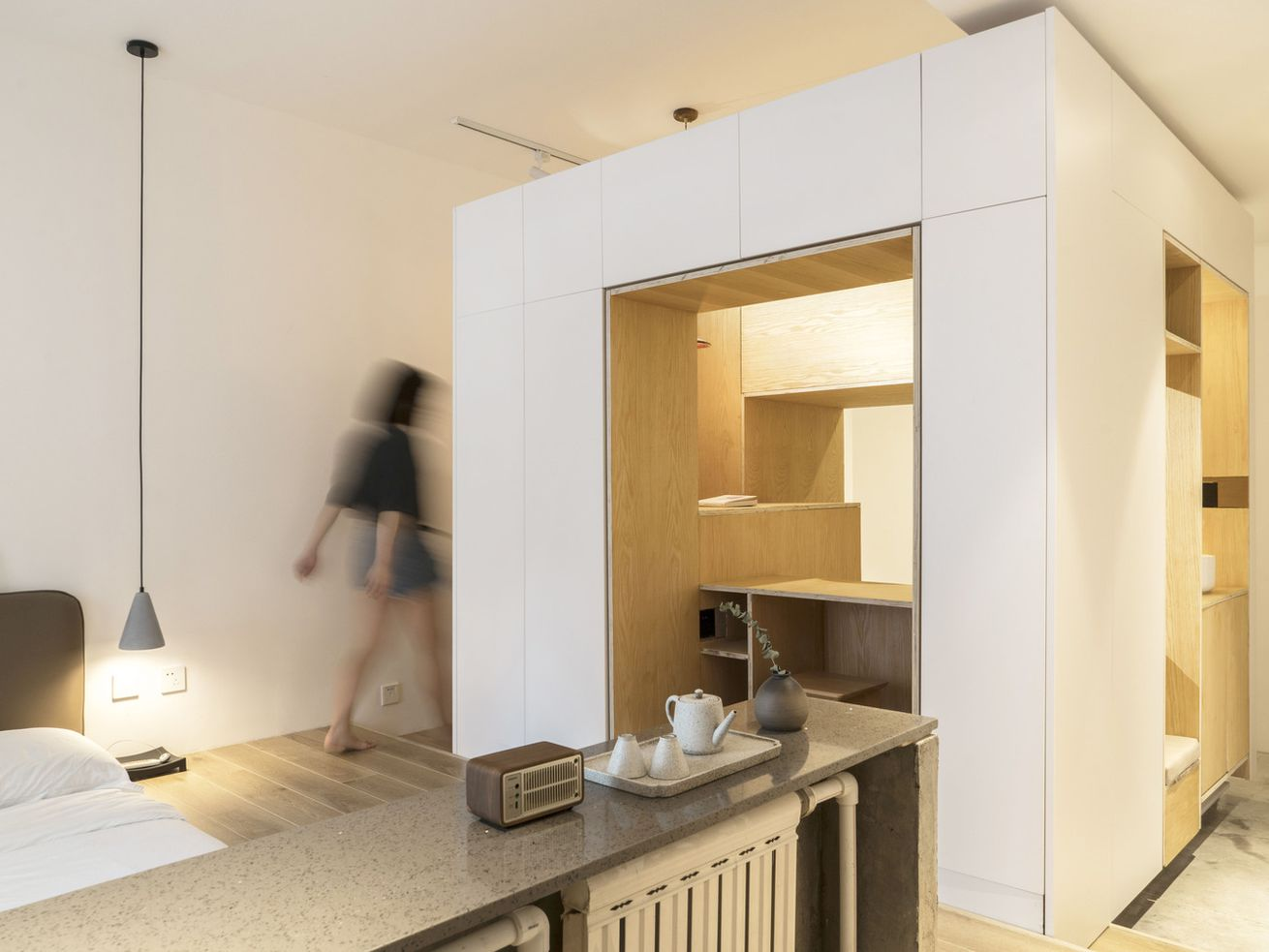Woman walking through compact apartment; a central module includes storage, surface area, and seating.