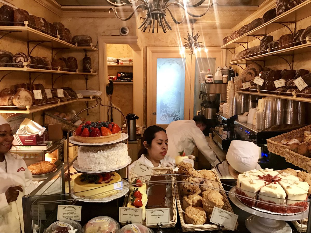 A snug baking operation with loaves of bread and other pastries stacked on shelves that stretch the ceiling. In the foreground, slices of cakes rest on platters.