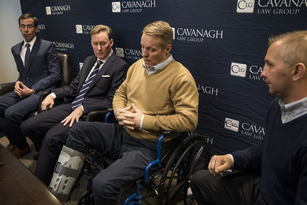 Attorney Tim Cavanagh (left) and Tomasz Stacha (right) look on as John Sherwood speaks to reporters about his injuries, including a broken ankle. | Ashlee Rezin / Sun-Times
