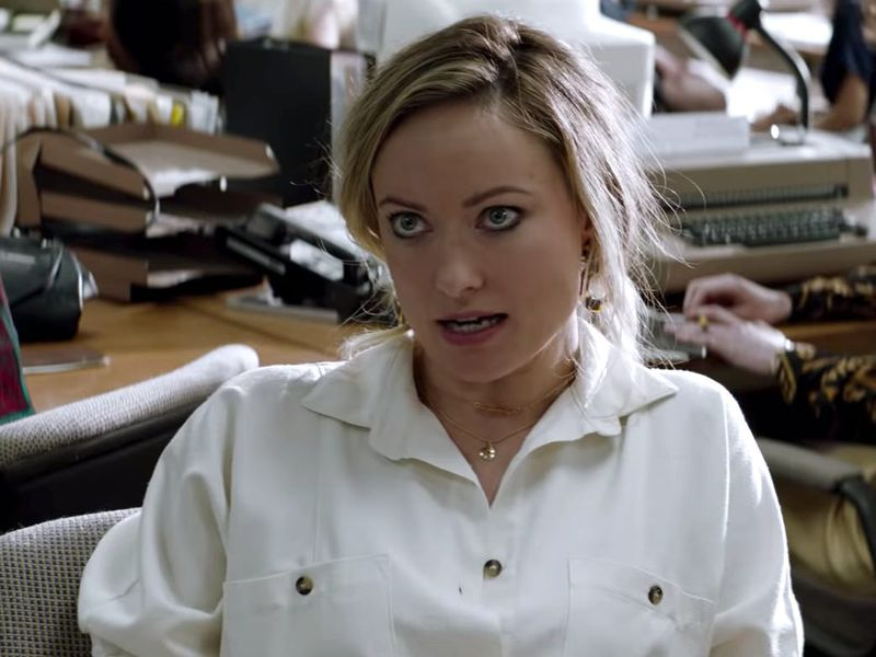 Playing journalist Kathy Scruggs, Olivia Wilde wears a white shirt and sits in a newsroom.