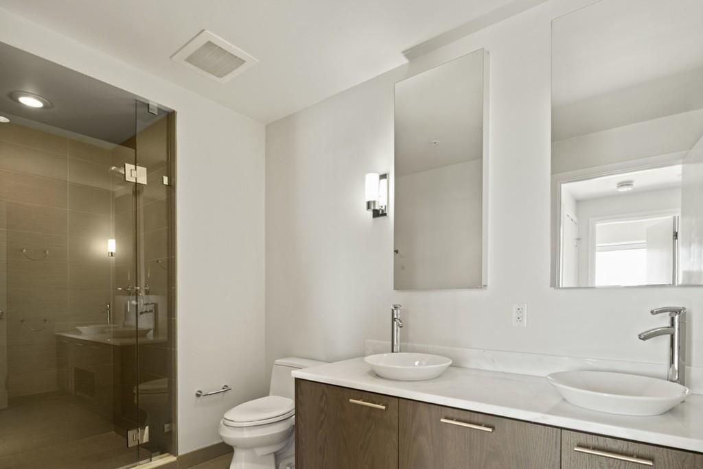 A bathroom with a large glass-doored shower, two basin sinks, and a large mirror.