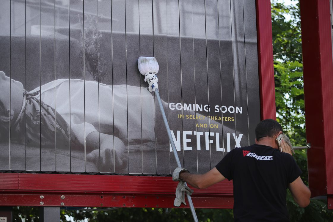 "A worker puts up a Netflix billboard with a picture of a person lying on the ground and the words, ""Coming soon in select theaters and on Netflix."""