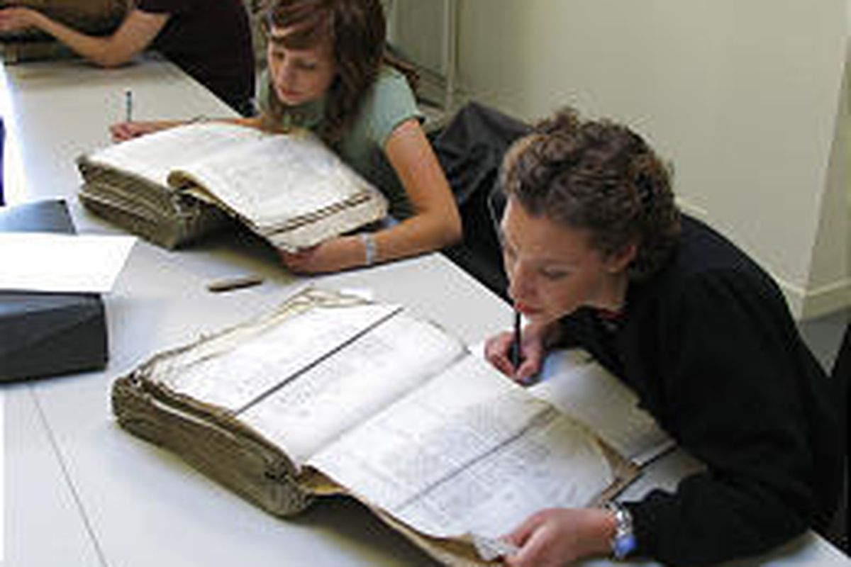 Students Ann Sumsion, front, and Anna Siebach transcribe 500-year-old account records in the Lille, France, archives.