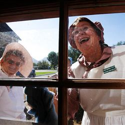 Dawn Warenski, left, and Linda Quitner laugh as they clean a window of a recently refurbished historic cabin in Santaquin.