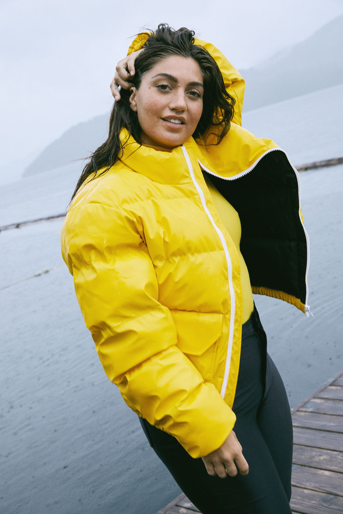A model wears a yellow puffer jacket on a dock on a lake.