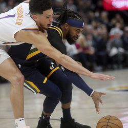 Phoenix Suns guard Devin Booker (1) and Utah Jazz guard Mike Conley (10) reach for the ball during an NBA game at the Vivint Smart Home Arena in Salt Lake City on Monday, Feb. 24, 2020.