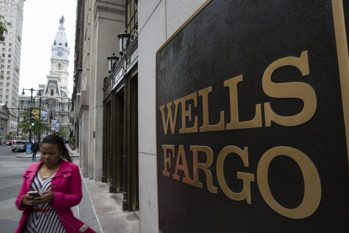 A woman walks past a Wells Fargo location in view of City Hall, left, in Philadelphia, Thursday, May 11, 2017.