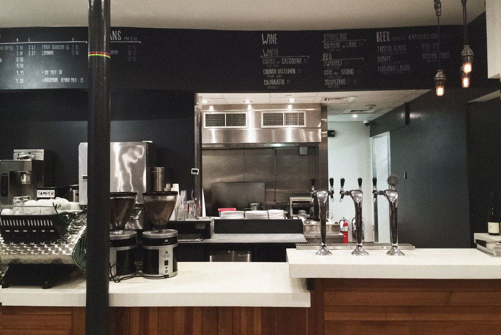 Wide shot of a coffee bar with a dark wood base, white counter, and a view of the kitchen in the rear, which has black walls and a dark overhanging menu board