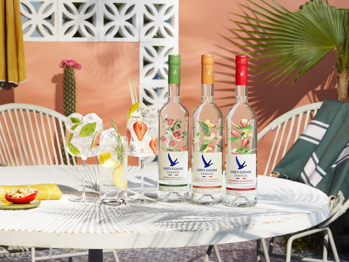 The three Grey Goose Essences flavors on a white patio table outdoors with a palm frond and cactus in the background.
