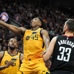 Utah Jazz guard Donovan Mitchell (45) goes for a long layup in the first half past Houston Rockets forward Ryan Anderson (33) as the Utah Jazz host the Houston Rockets at Vivint Smart Home Arena in Salt Lake City on Thursday, Dec. 7, 2017.