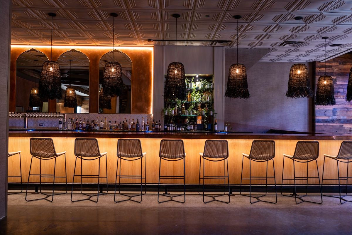 14 backed stools sit along a bar that's lit from underneath