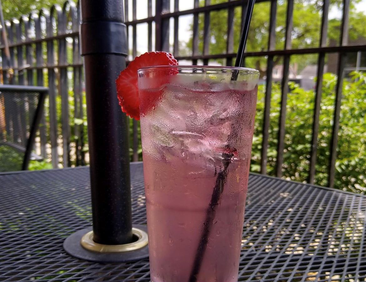 A light pink cocktail in a tumbler glass topped with a strawberry slice on a wrought iron outdoor table