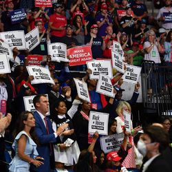 """Governor Kevin Stitt claps among """"Black Voices for Trump"""" supporters as US President Donald Trump speaks during a campaign rally at the BOK Center on June 20, 2020 in Tulsa, Oklahoma. - Hundreds of supporters lined up early for Donald Trump's first political rally in months, saying the risk of contracting COVID-19 in a big, packed arena would not keep them from hearing the president's campaign message."""