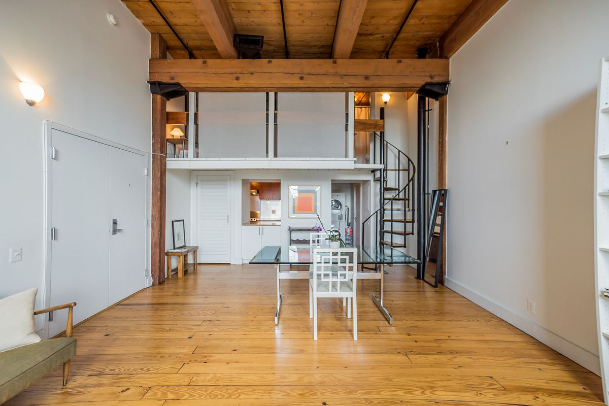 A loft condo in Philadelphia with wooden ceilings, a spiral staircase, and hardwood floors.