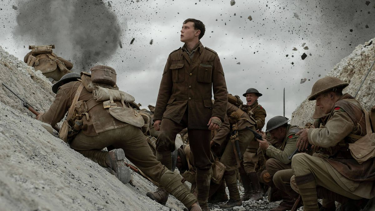 Schofield (George MacKay) stands in a trench amidst other soldiers and falling debris in 1917