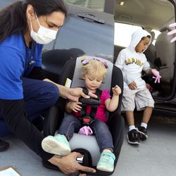 Certified child passenger safety technician Jesus Cruz fits 2-year-old Mayleigh Brown into a new car seat during a drive-thru checkpoint atShriners Hospitals for Children - Salt Lake Cityon Friday, Sept. 25, 2020. The checkpoint was an extension of the hospital's ongoing special needs car seat clinic, and a way to give back to the community.