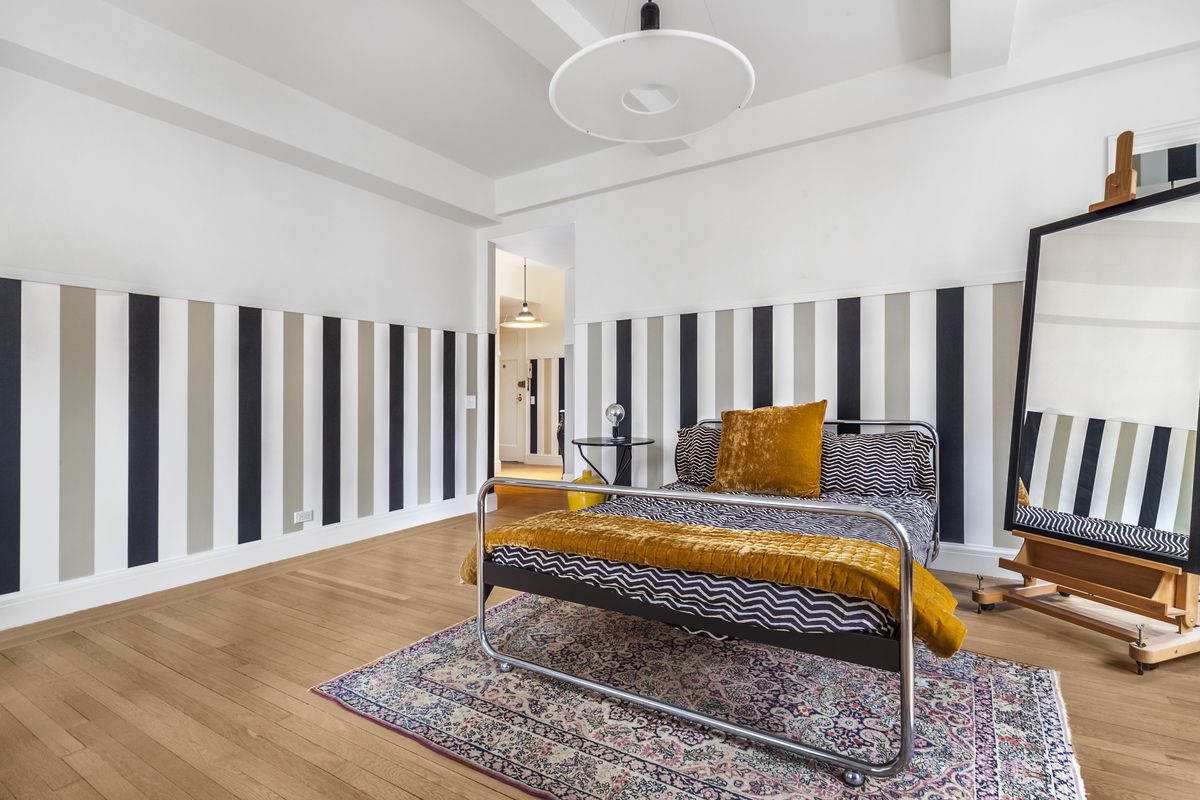 A living area with a small bed, a colorful rug, a standing mirror, beamed ceilings, and vertical stripes on its walls.