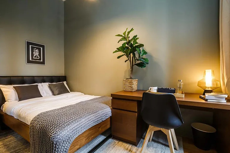 A bedroom with a large bed, a wooden desk with a chair, a planter, and dark green walls.