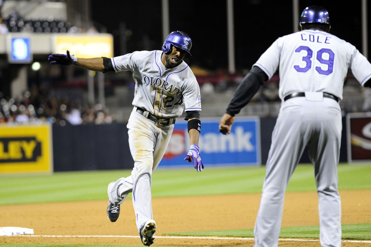 Dexter Fowler rounds third base and celebrates with Stu Cole after his ninth-inning home run off Huston Street Friday. The home run was his second of the game and sixth of the season.