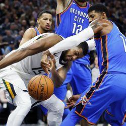 Utah Jazz forward Derrick Favors and Oklahoma City Thunder forward Paul George fight for a loose ball during NBA basketball in Salt Lake City on Saturday, Dec. 23, 2017.