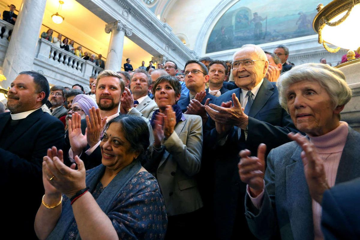 Elder L. Tom Perry, a member of the Quorum of the Twelve Apostles of The Church of Jesus Christ of Latter-day Saints, right, joins equal rights activists, clergy, and others in a round of applause after Governor Gary Herbert signed SB296 at the Capitol in