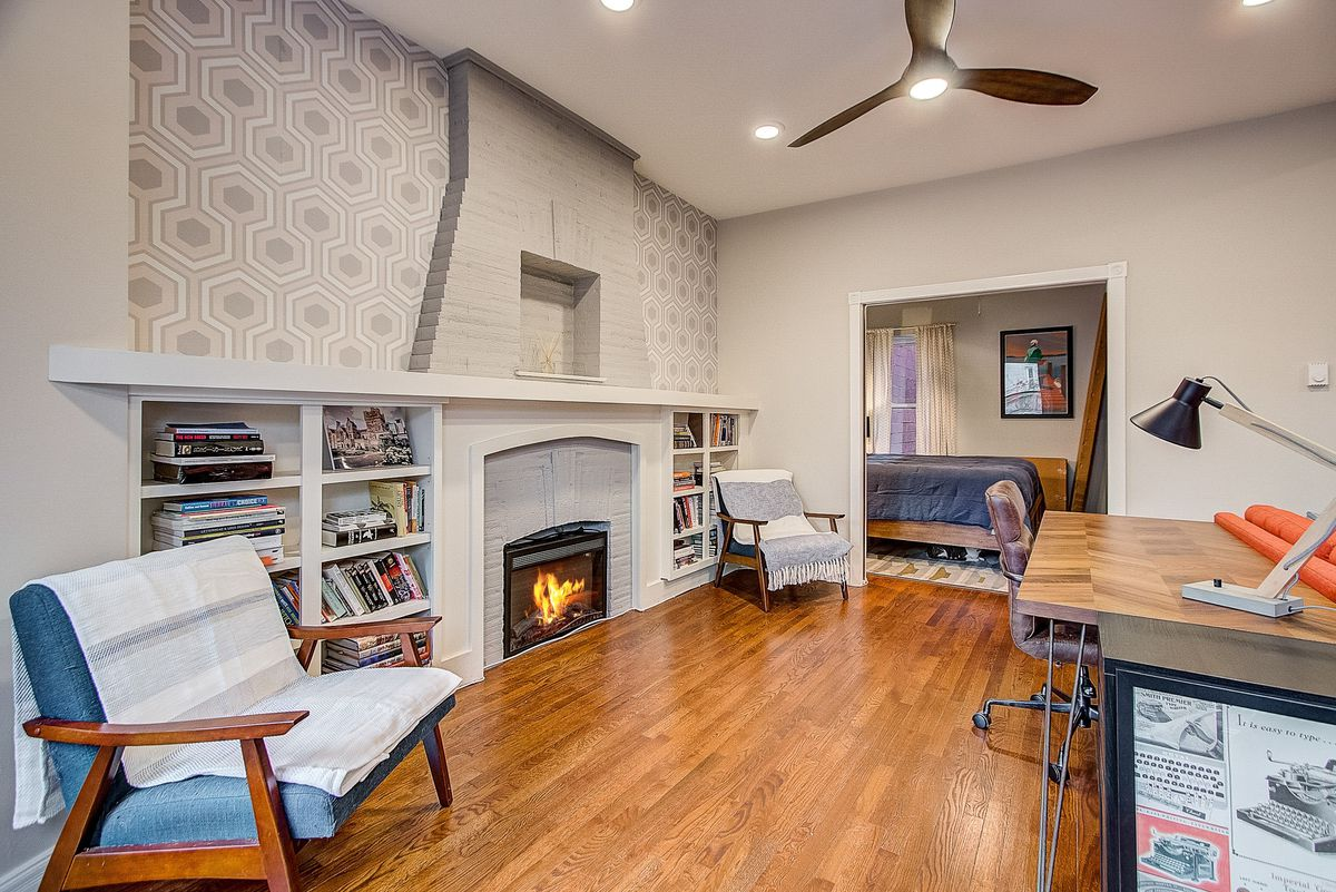 A view of the fireplace and living room with a workspace. The bedroom is in the background.