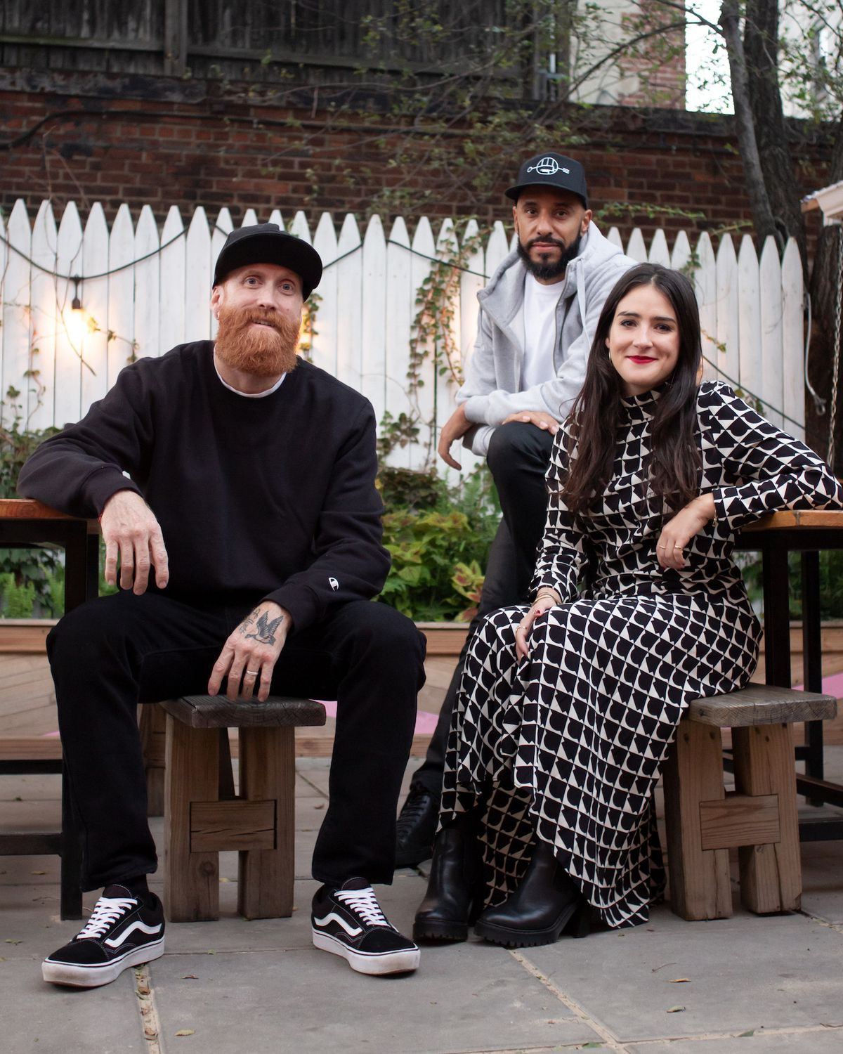 Three people sitting in a backyard are looking into the camera for a portrait style photo