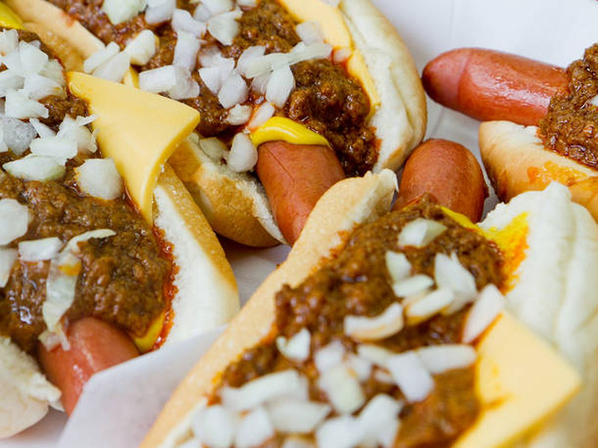 Pinks hot dogs cornered together with lots of chili and onions and cheese.