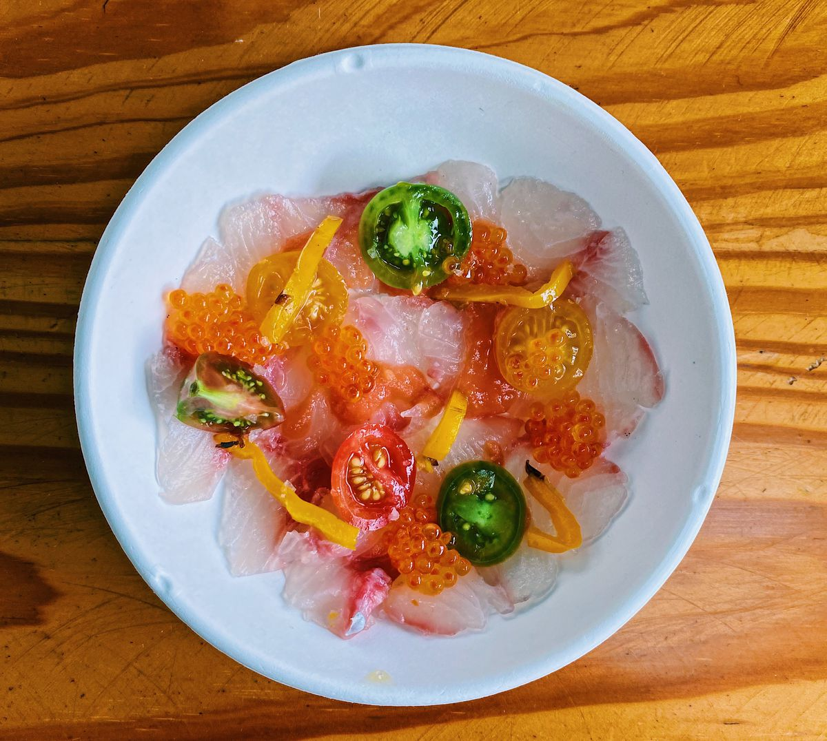 A white bowl filled with fish, colorful tomatoes, and orange trout roe set on a wooden table