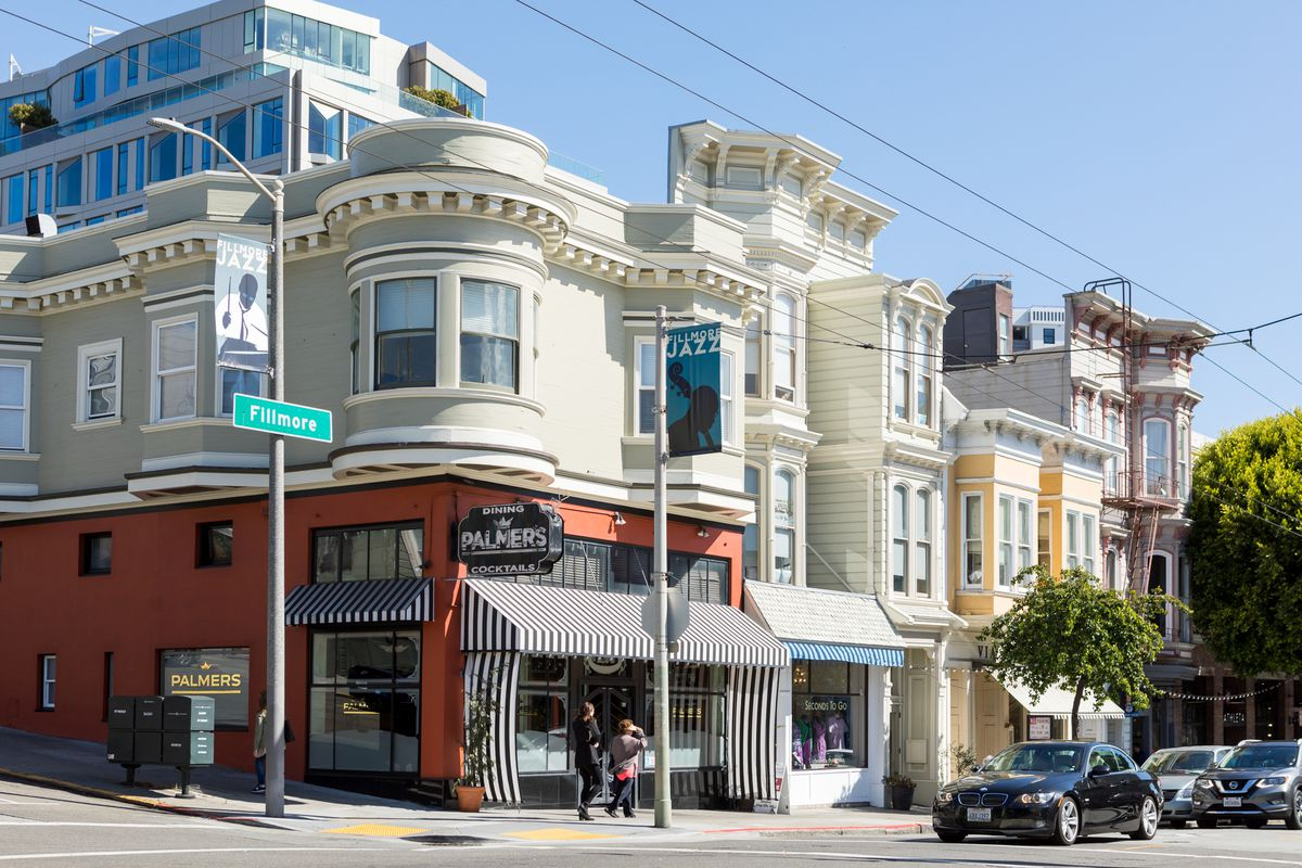 A street in San Francisco. The building on the corner has a black and white striped awning and a red and white facade. There is a street sign in front of the house which reads: Filmore. There are people walking on the sidewalk.