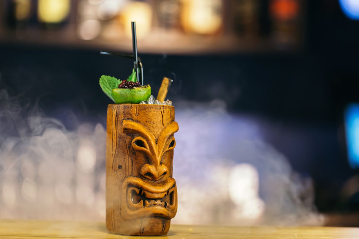A cocktail served in a tiki mug and garnished with ice, mint, cinnamon stick, and lime