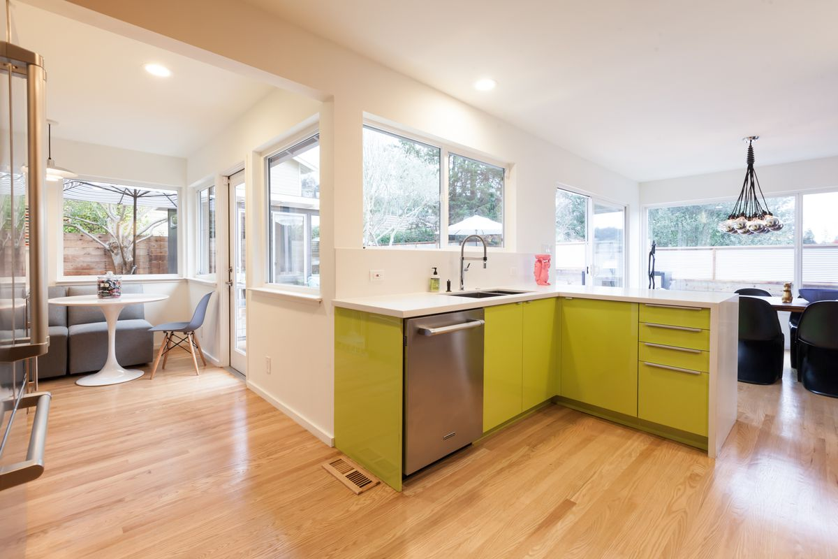 A kitchen dining area with lime green cabinetry, a table and chairs, and a chandelier.