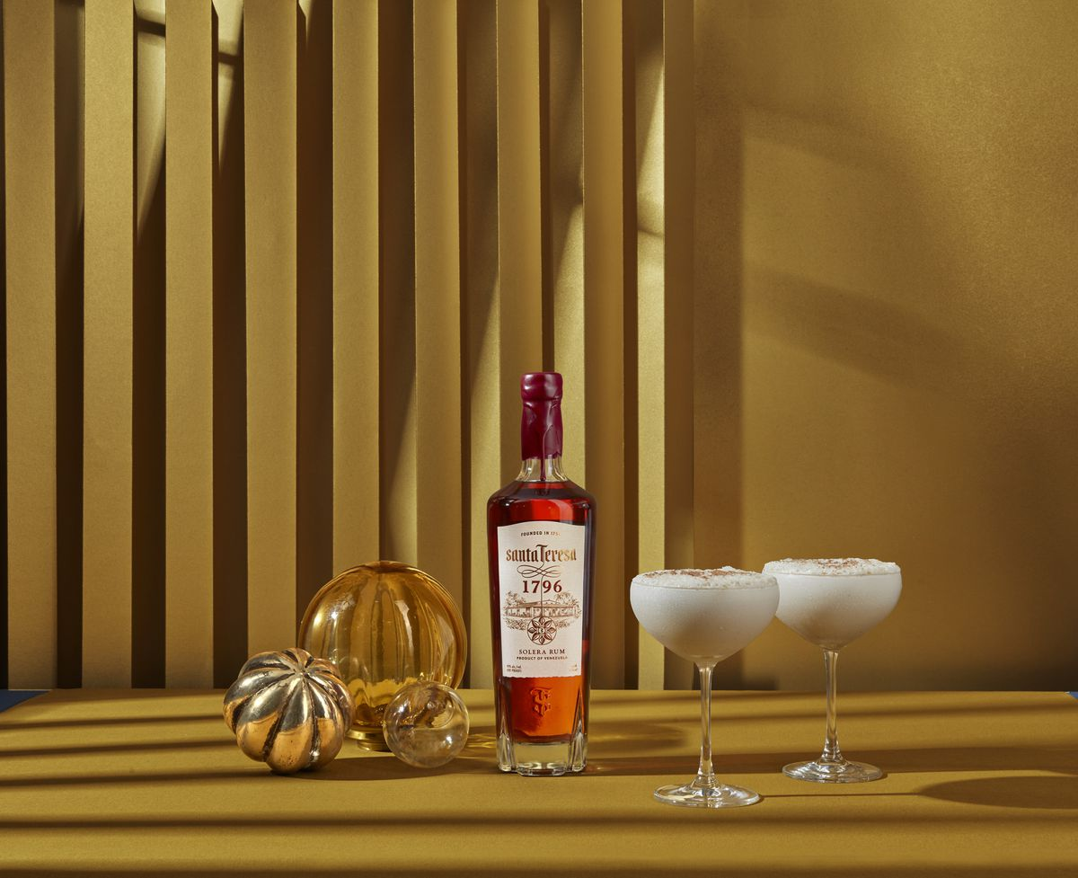 Against a golden-brown background sit a tall red bottle of alcohol along with two wine glasses that have a white drink in them