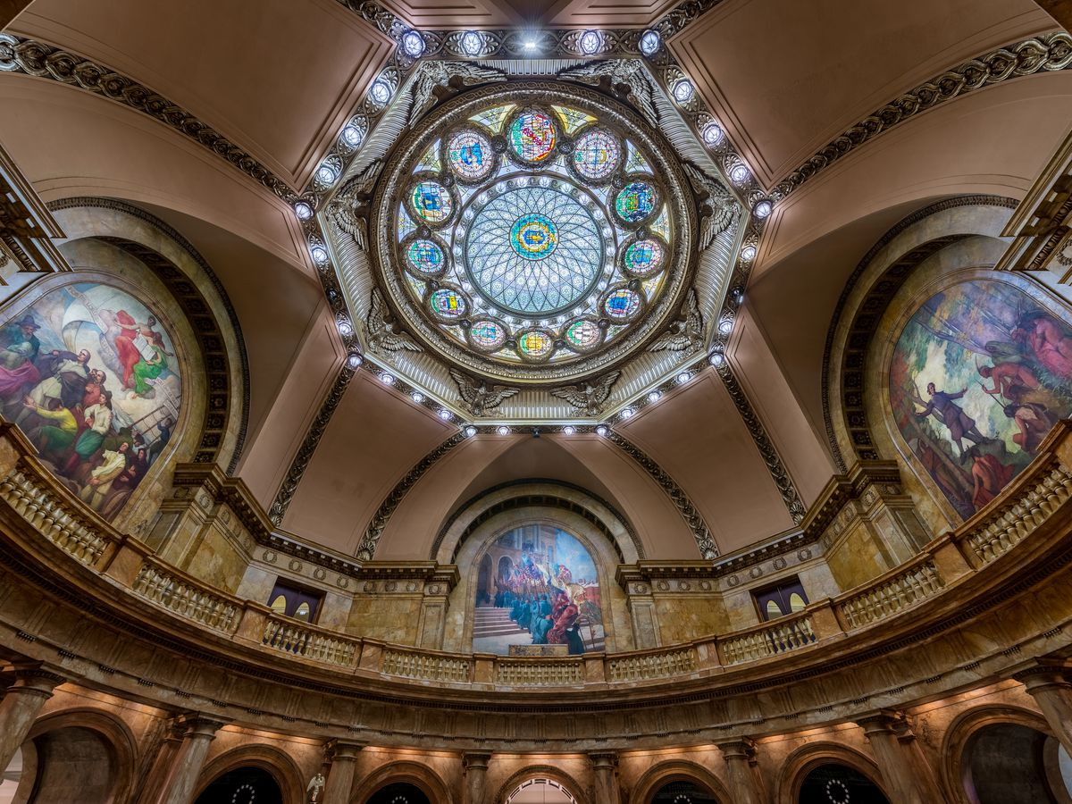 Looking up at a high-ceilinged cupola with stained glass at the center.