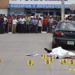 People watch as the body of human rights District Attorney Manuel Eduardo DÍaz Mazariegos, lies dead after he was gunned down in Choluteca, Honduras, Monday Sept. 24, 2012. A day earlier, Antonio Trejo Cabrera, a prominent Honduran human rights lawyer was also gunned down in the capital city of Tegucigalpa. (AP Photo)