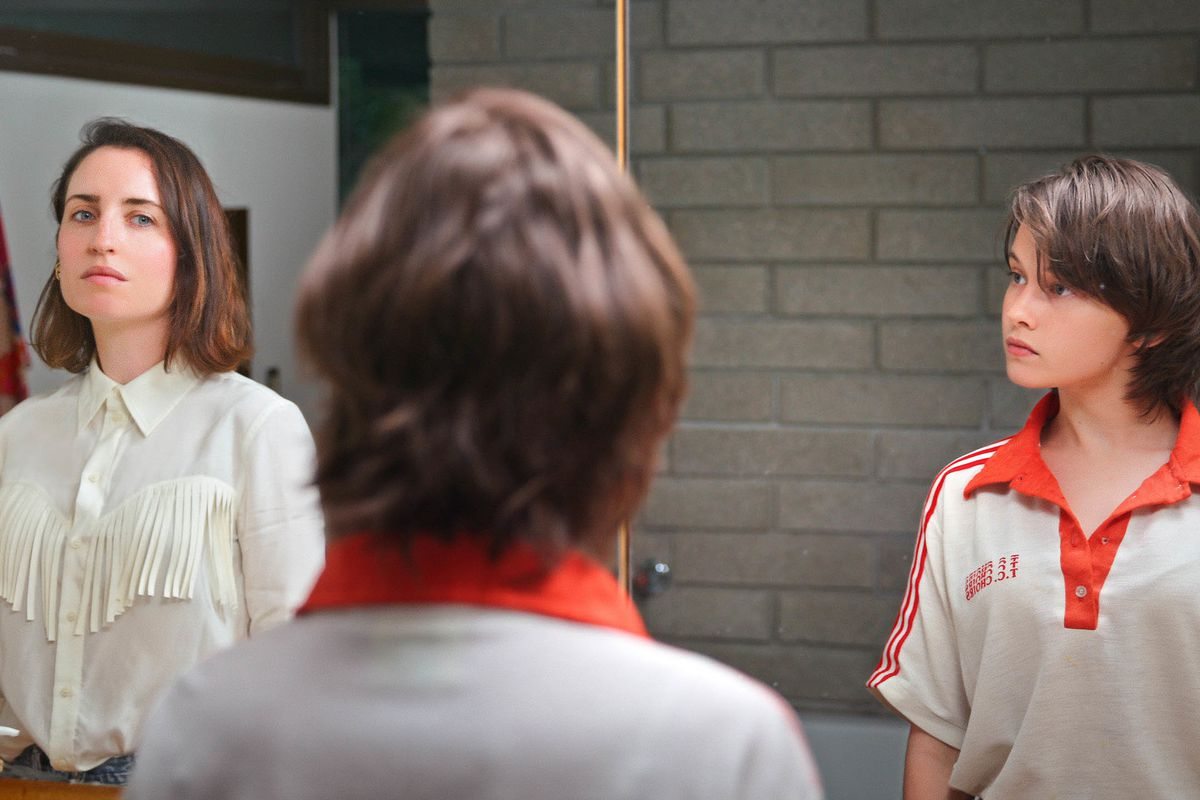 Zoe Lister-Jones and Cailee Spaeny stand in front of the same mirror, taking a moment before preparing for a party in How It Ends