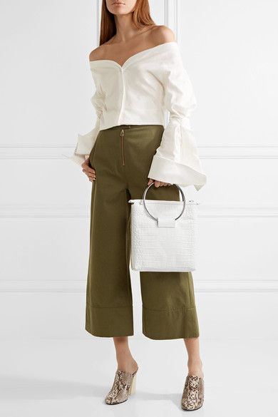 A model wearing green pants, a white shirt, and carrying a white bag