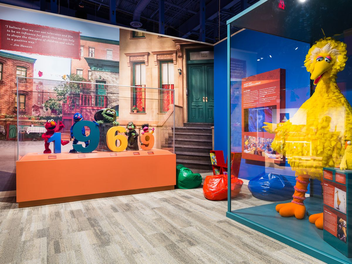 In the foreground is a glass display case with the puppet Big Bird from Sesame Street. In another glass display case are colorful statues of the numbers 1, 9, 6, 9 with various Sesame Street puppets flaking the numbers. The puppets are Oscar the Grouch, E