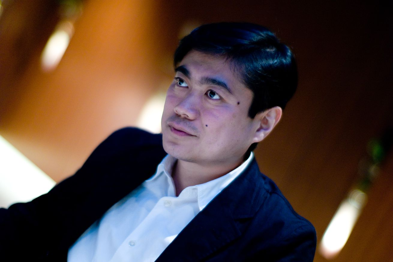 Joi Ito looks off-camera with a solemn expression