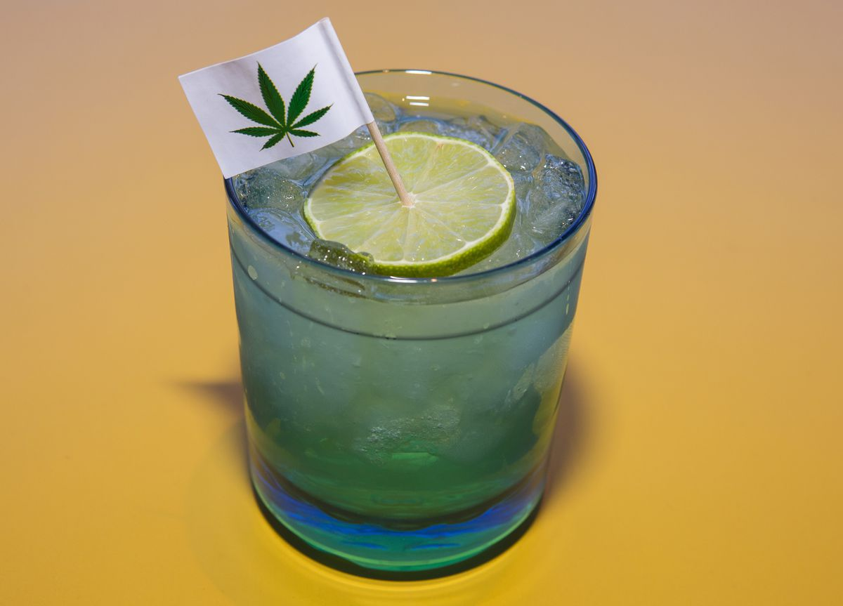 A clear cocktail and a light blue glass with a flag with a marijuana leaf embedded in a lime slice.