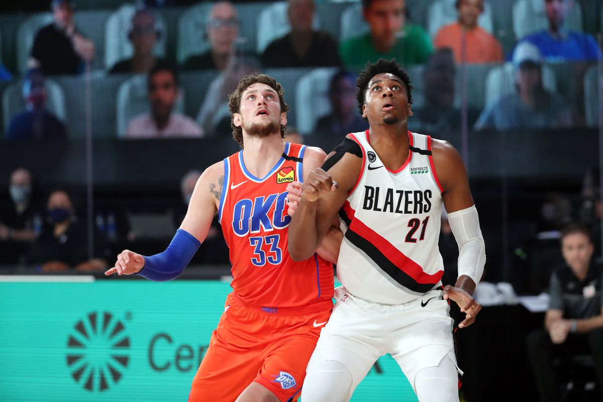 Mike Muscala of the Oklahoma City Thunder and Hassan Whiteside of the Portland Trail Blazers fight for position during a scrimmage on July 28, 2020 at The Visa Athletic Center at ESPN Wide World Of Sports Complex in Reunion, Florida.