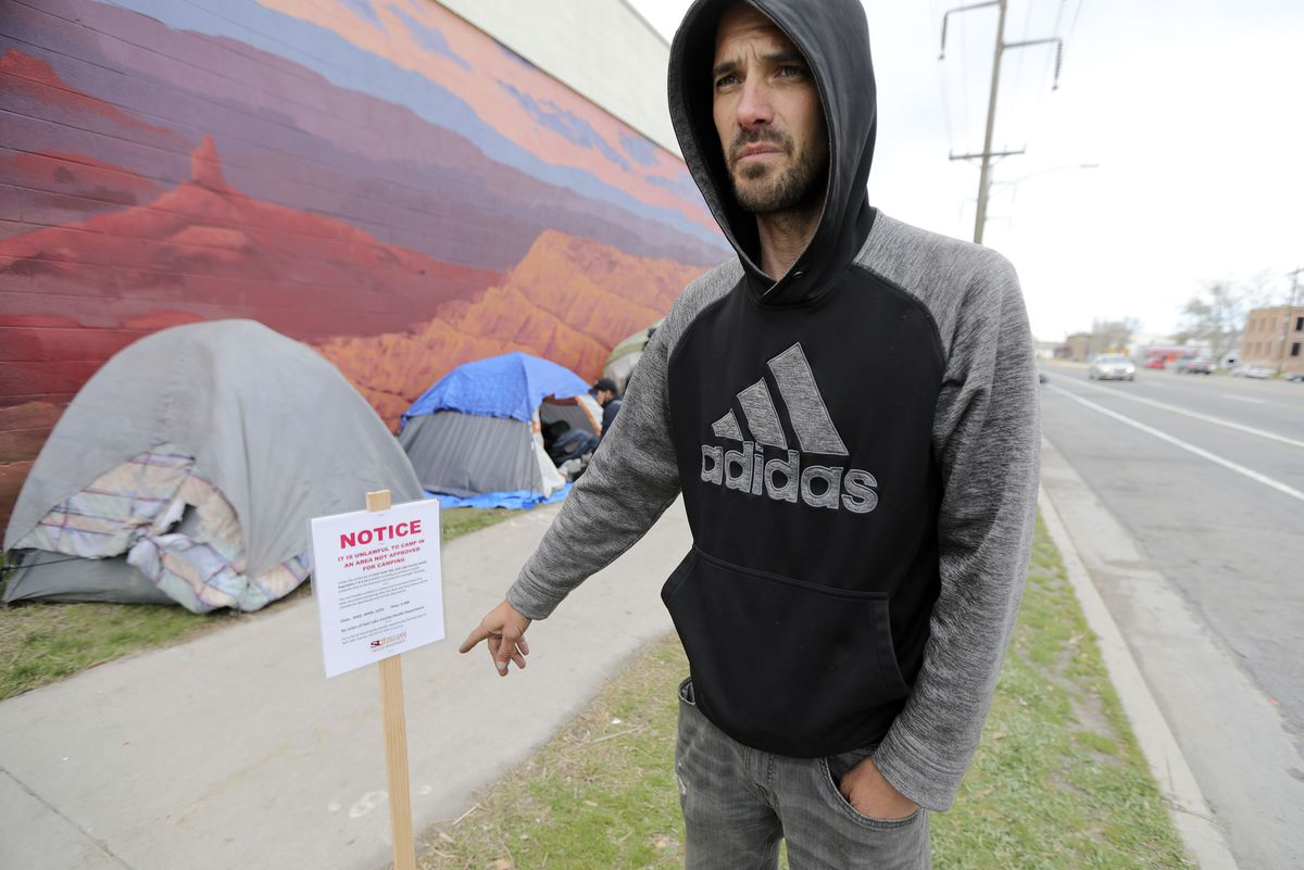 Andrew Blackburn, who has been homeless for about a year, points to a newly posted sign on 800 South in Salt Lake City on Tuesday, April 13, 2021, alerting members of the homeless community they need to move their camps by 9 a.m. Wednesday.